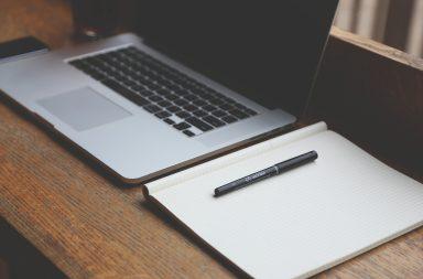 Laptop und Notizbuch mit Stift