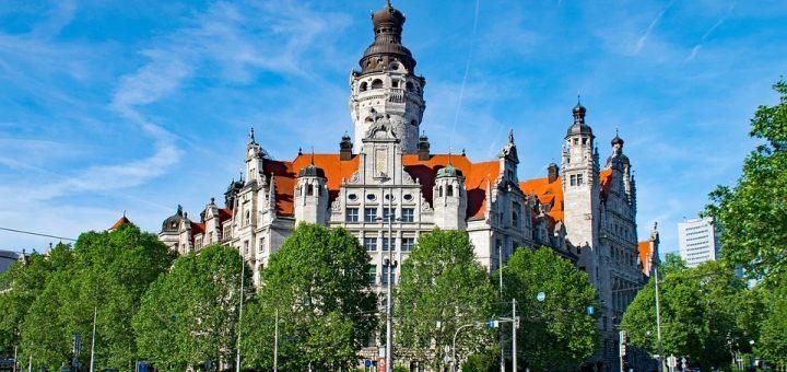 Das neue Rathaus Leipzigs, umgeben von grünen Bäumen bei blauem Himmel