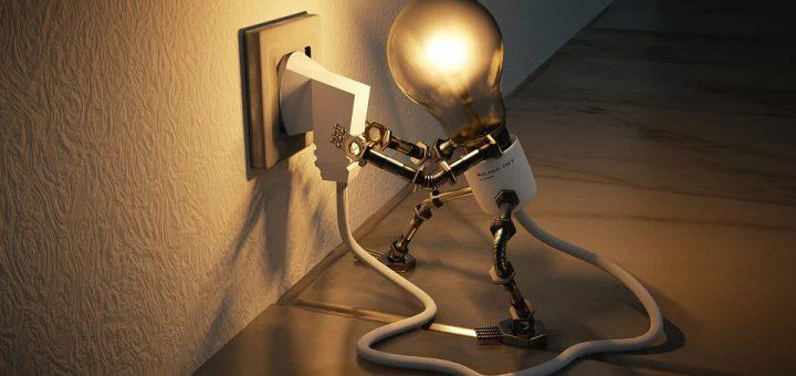 Eine Figur in Form einer Glühbirne steckt den mit dem eigenen Körper verbundenen Stecker in eine Steckdose und leuchtet