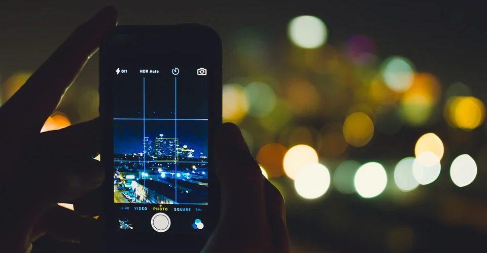 Im Vordergrund wird ein Smartphone mit geöffnetem Kameramodus ins Bild gehalten, durch das Display ist eine Stadt bei Nacht zu sehen