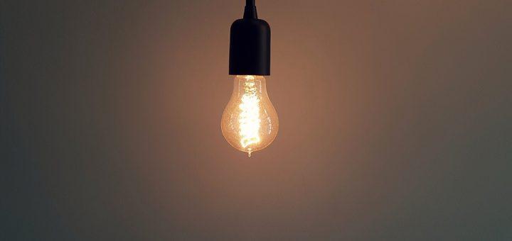 warm leuchtende Glühbirne die an einem schwarzen Kabel hängt