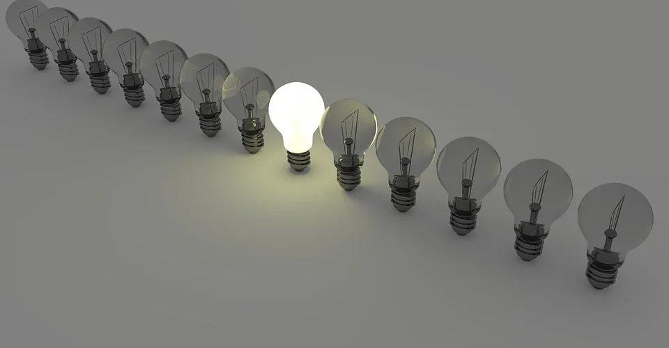 eine Reihe von Glühbirnen auf weißem Hintergrund, nur die mittlere ist erleuchtet