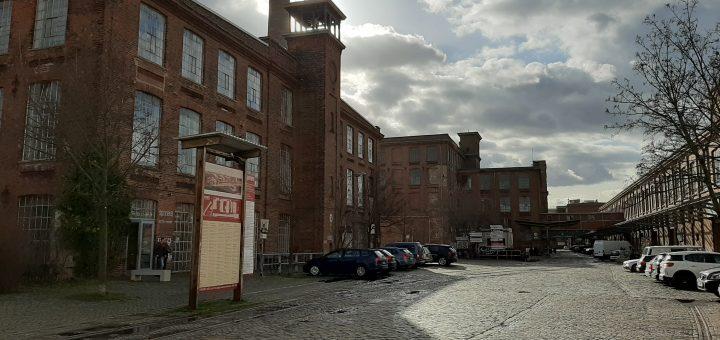 Links Gebäude der Baumwollspinnerei aus Backsteinen, rechts im Bild führt eine gepflasterte, unbefahrene Straße am Gebäude vorbei, an den Seiten parken Autos