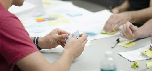 Blick über die Schulter einer Person, die an einem Tisch mit vielen Dokumenten, Stiften und einer Wasserflasche sitzt und einen Zettel in den Händen hält